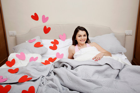 housing lot: Woman in bed with heart shapes on bedclothes