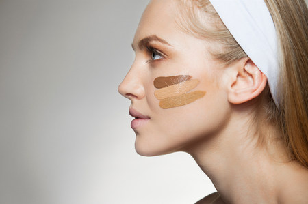 Woman with stripes of foundation on cheek