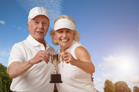 Senior couple holding tennis trophy