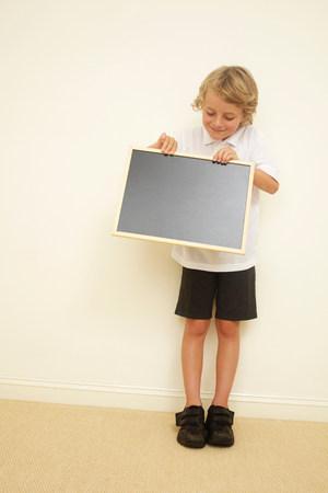Schoolboy holding blank blackboard