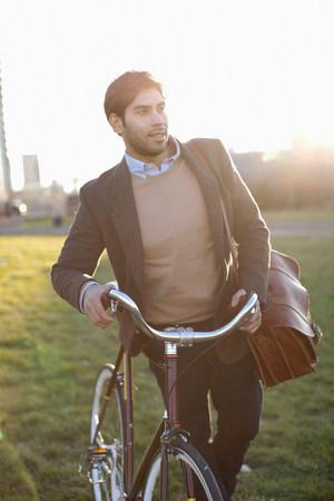 environmentalism: Man pushing bicycle in grass