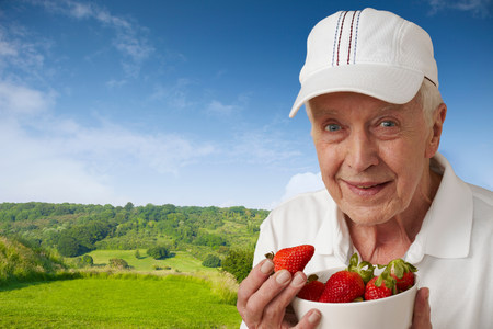 70s tennis: Senior man in tennis clothes with strawberries against rural scene