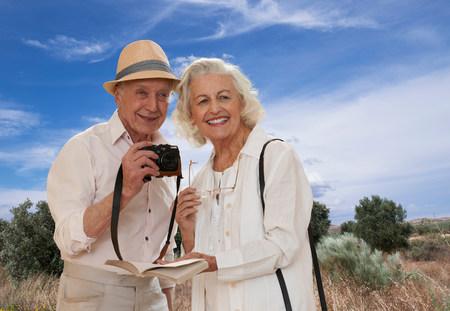 Senior couple exploring landscape with camera