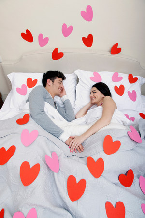 Couple in bed with heart shapes on bedclothes LANG_EVOIMAGES