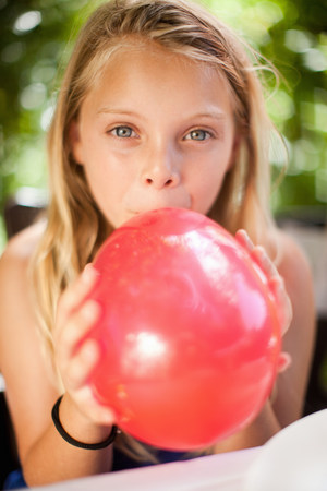 good color: Girl blowing up balloon at party