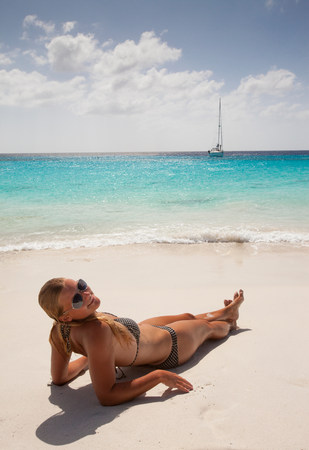 Smiling woman sunbathing on beach LANG_EVOIMAGES