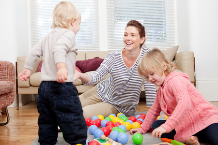 housing lot: Mother and children playing with plastic balls