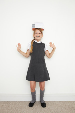 gifted: Schoolgirl balancing books on her head LANG_EVOIMAGES