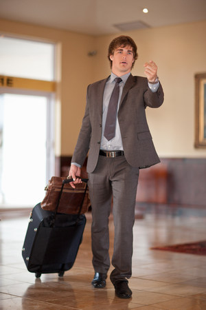 hurried: Businessman rolling luggage in lobby