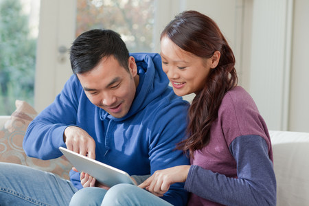 30 years old married couple: Couple using tablet computer together