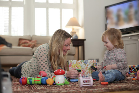 woman hanging toy: Mother and daughter playing with toys on living room floor LANG_EVOIMAGES