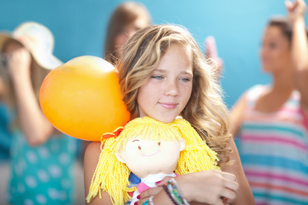 tweens: Smiling girl holding balloon and doll LANG_EVOIMAGES