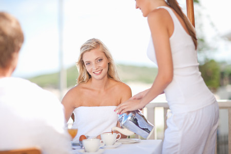 Waitress serving woman coffee at table