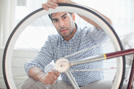 30 years old man: Man fixing bicycle wheel indoors