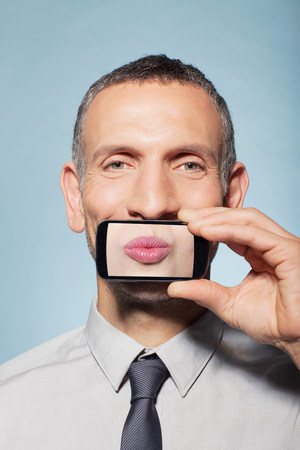 puckered lips: Man covering mouth with smartphone LANG_EVOIMAGES