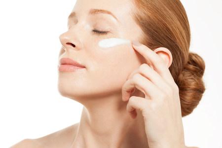 shutting: Woman applying moisturiser with eyes closed