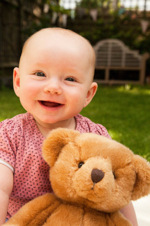 Happy baby girl with teddy bear