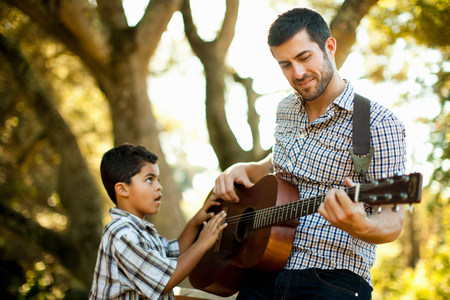 level playing field: Father and son playing guitar together
