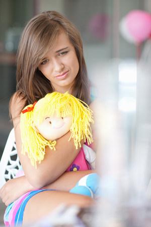 Sad teenage girl hugging doll