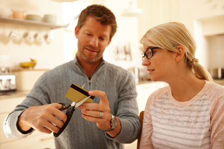 decide deciding: Couple cutting credit card with scissors