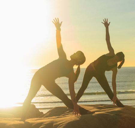 Two women practising yoga on beach in sunlight