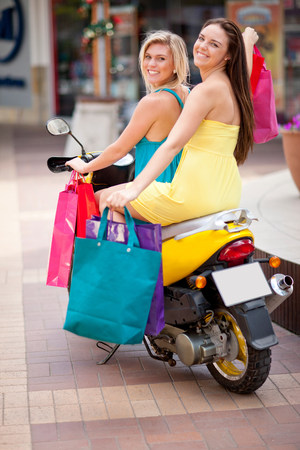 Women carrying shopping bags on scooter