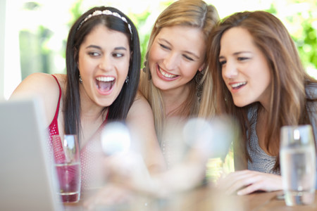 silliness: Smiling women using laptop together LANG_EVOIMAGES