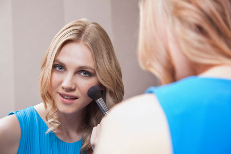 Young woman applying blusher in the mirror