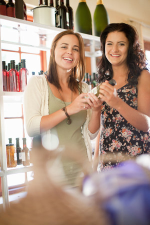 Women holding vinegar bottle in grocery LANG_EVOIMAGES
