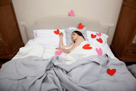 housing lot: Woman asleep in bed with heart shapes on bedclothes