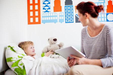 Mother holding digital tablet,daughter in bed
