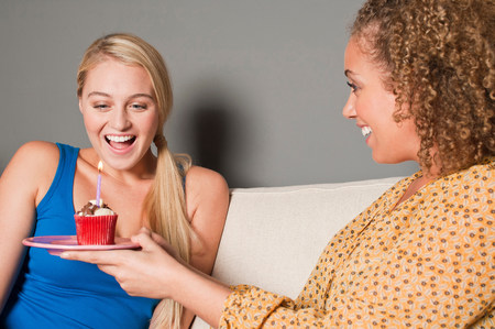 give out: Woman giving friend cupcake