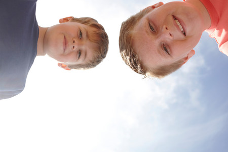 age 10 12 years: Two boys looking at camera,viewed from below