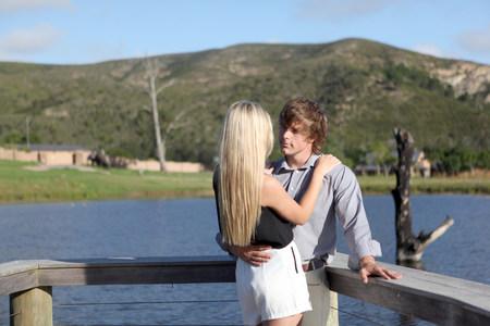 Couple hugging on wooden deck LANG_EVOIMAGES
