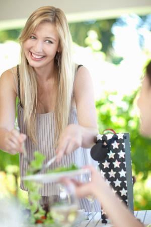 detoxing: Woman serving salad at table
