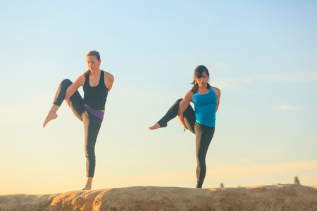 Two women practising yoga on top of a rock