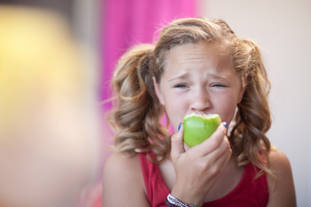 wincing: Close up of girl eating apple