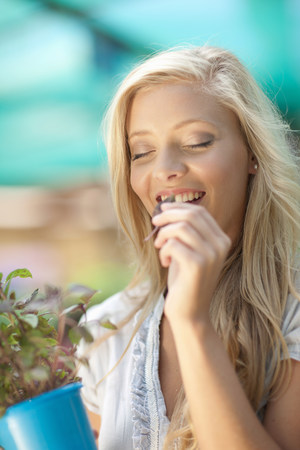 Woman smelling plant in nursery LANG_EVOIMAGES
