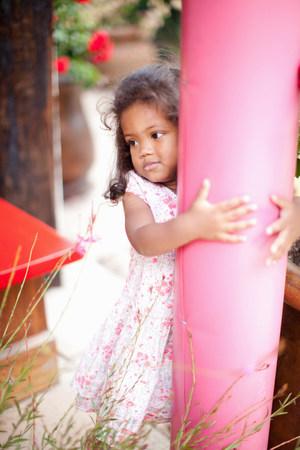 Girl hugging pole outdoors LANG_EVOIMAGES