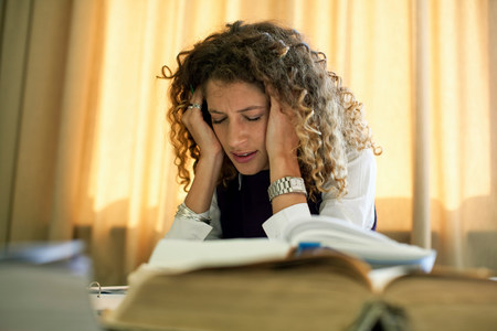 Frustrated woman studying at desk