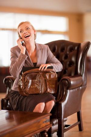 pubertad: Empresaria en el teléfono celular en el vestíbulo