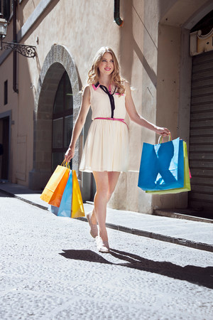 Young woman on street with shopping bags LANG_EVOIMAGES