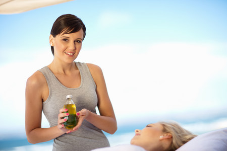 Masseuse holding bottle of oil outdoors