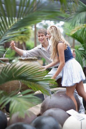 Man splashing girlfriend in fountain LANG_EVOIMAGES