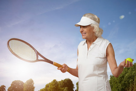 70s tennis: Senior woman with tennis racket and ball LANG_EVOIMAGES