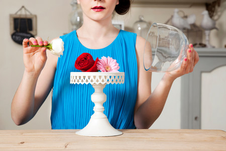 frailty: Woman lifting lid of cake stand with flowers