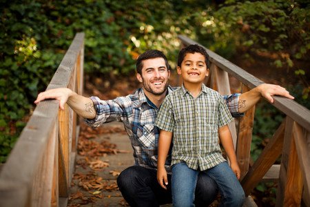 giggling: Father and son playing on wooden bridge LANG_EVOIMAGES