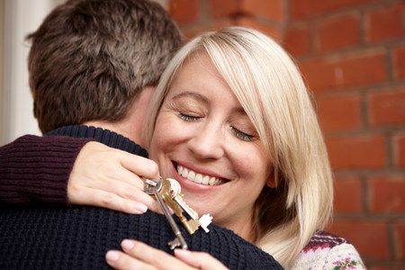 Couple hugging,woman holding house keys LANG_EVOIMAGES
