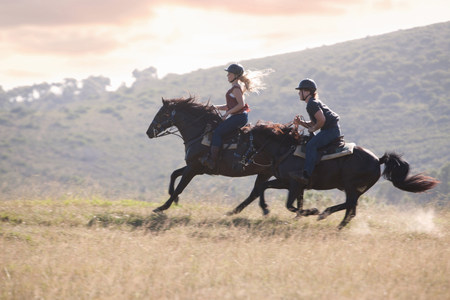 run down: Couple riding horses in rural landscape LANG_EVOIMAGES