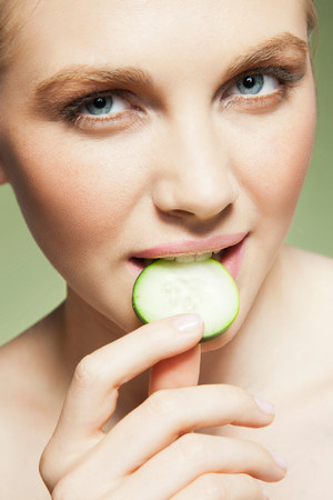 Woman biting piece of cucumber LANG_EVOIMAGES